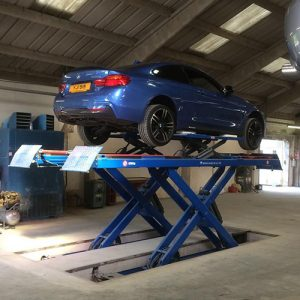 Blue BMW on scissor lift rear side view